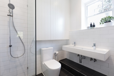 white bathroom with double sink and toilet